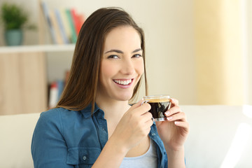 Woman drinking coffee looking at camera at home