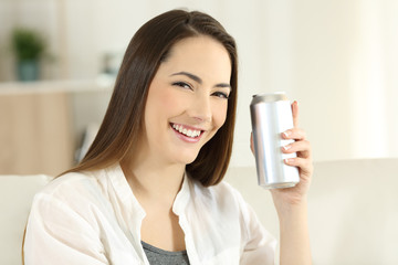 Woman showing a refreshment can at home