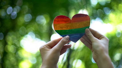 Rainbow heart in female hands, LGBT flag, recognition of sexual minorities right