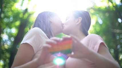 Happy lesbian couple in love kissing, holding rainbow heart, LGBT pride flag
