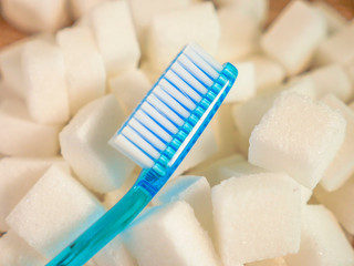 isolated conceptual still life image of toothbrush over massive pile of sugar cubes in dental care and oral hygiene concept as warning on sweet nutrition abuse