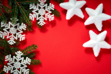 beautiful christmas white stars on a red background with twigs of spruce