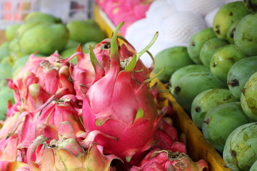 Colourful display of pink dragonfruit also called Pitaya, green mangoes and papayas on a fruit stand in Indonesia