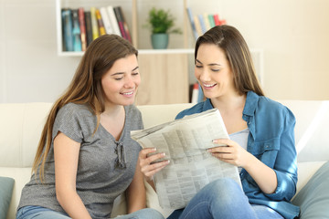 Two friends reading newspaper together at home