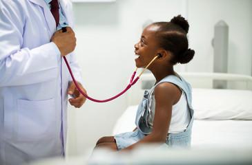 Friendly pediatrician entertaining his patient Fototapete