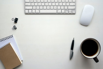 White wooden table with keyboard, mouse, pen, notebook, document clips and a cup of coffee. Workspace top view with copy space.