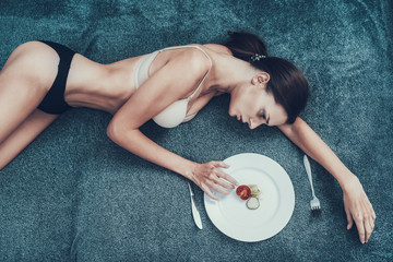 Slim Girl with Anorexia Lying on Sofa with Plate.