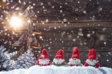 Vier Nikolausfiguren im Schnee vor alter Holzwand