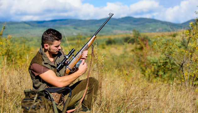 Hunting shooting trophy. Hunter with rifle looking for animal. Hunting hobby and leisure. Man charging hunting rifle. Hunting equipment concept. Hunter khaki clothes ready to hunt nature background