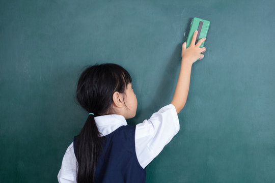 Asian Chinese little girl wiping the green blackboard