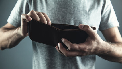 Caucasian man holding empty leather wallet.