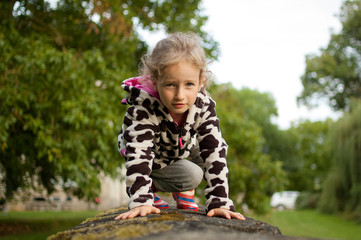 Beautiful curly girl sitting on a stone fence in the village. Play Tiger. Girl on the fence