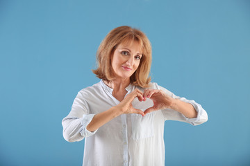 Portrait of mature woman making heart with her hands on color background