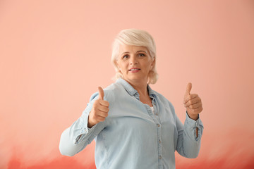 Portrait of mature woman showing thumb-up on color background