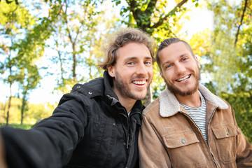 Happy gay couple taking selfie in park