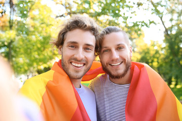 Happy gay couple taking selfie with rainbow LGBT flag in park