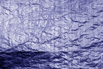 Crumpled transparent plastic  surface in blue color.