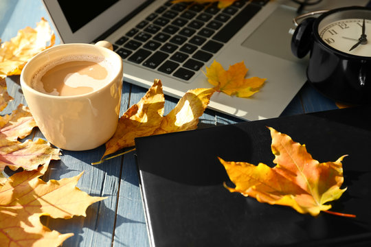 Laptop with coffee, book and autumn leaves on wooden table