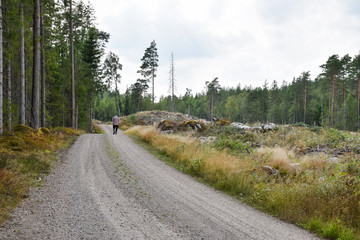 Male person walks on a gravel road