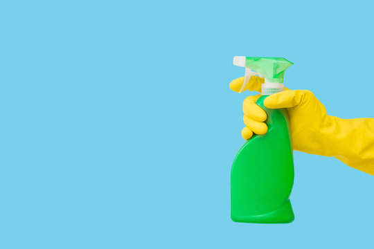 Cleaner's hand in yellow rubber protective glove holding plastic spray bottle on blue background. General or regular cleanup. Commercial cleaning company. Empty place for text or logo.