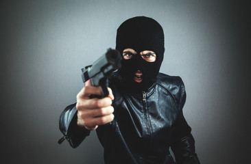 Aggressive man in a black mask with a pistol. - fototapety na wymiar