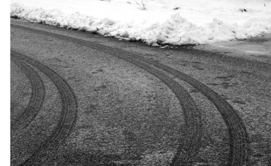 Car tyre prints on frosty road in black and white.