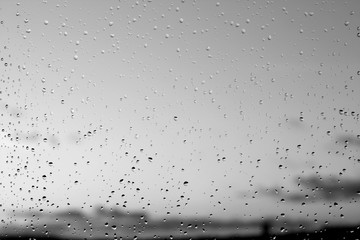 Rain drops and defocused sky background in black and white.