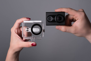 hands holding black action camera and waterproof case on grey background
