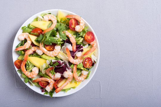 Mix of salad with shrimps , avocado and cherry tomatoes