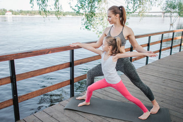 Young woman supports her small student. They are stretching together. Girls are pulling hands to the river. They are working out outside at bridge.