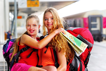 Traveller girl female wear headphones with backpack and tourism outfit paper map at railway station city outdoor. Terminal train locomotive on background.