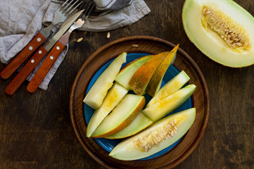 Melon. Fresh sliced melon in  a plate on  the wooden table. Top view flat lay background. Copy space.