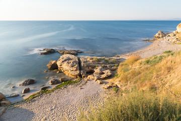 The wild sea beach with stones at sunrise. Bulgaria