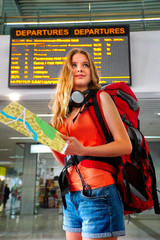 Traveller girl female wear headphones with backpack and tourism outfit paper map next to train display schedule board at railway station city outdoor. Terminal train locomotive on background.