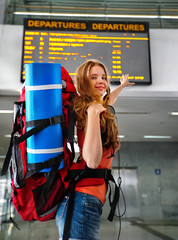 Traveller girl female with backpack and tourism outfit point to train display schedule board at railway station city outdoor. Terminal train locomotive on background.
