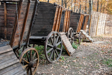 Old horse drawn wooden cart. Convoy of several carts in the autumn forest