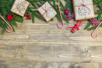 Christmas holiday border - gifts, holly berries and decoration on wooden board. Holiday card. Top view.