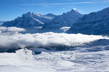 First snow and winter mountain landscape in mid october with clouds in the valley. Jungfrau region in Switzerland.