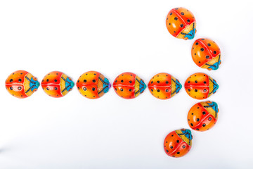 beautiful set of multicolored ladybugs forming an arrow in Mexican ceramics, top view, copy space, flat lay, space for text