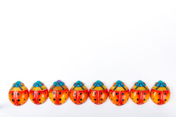 beautiful set of multicolored ladybugs forming in a straight line in Mexican ceramics, top view, copy space, flat lay, space for text