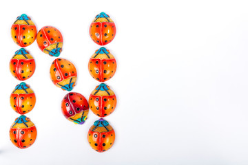 beautiful set of multicolored ladybugs forming an letter n in Mexican ceramics, top view, copy space, flat lay, space for text