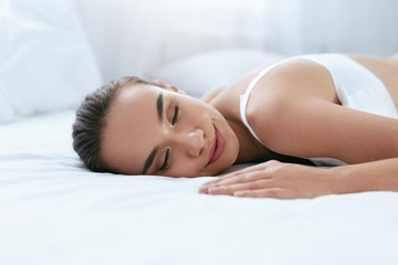 Beautiful Woman Sleeping On White Bed In Light Interior