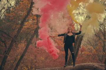 Girl with red and yellow smoke bombs in autumn