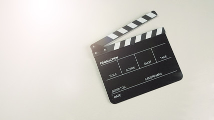 Clapper board or movie slate use in video production or movie and cinema industry in flare light. It's black color on white background.