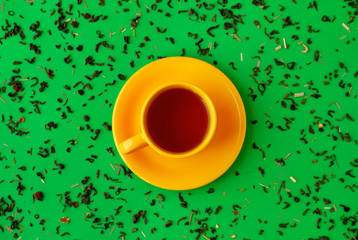 Cup of tea and tea leaves on a green background. View from above. A yellow cup of tea reminds of spring and summer. Green tea leaves on green background.