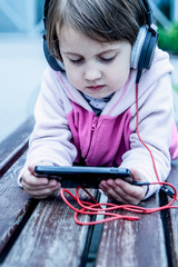Social Media addiction. Little child girl holding smart phone. Psychological problems and media mania concept.