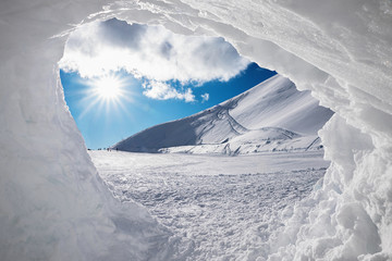 Blick aus der Schneehöhle auf verschneite Winterlandschaft mit Sonne Wall mural