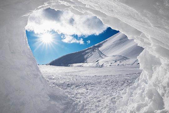 Blick aus der Schneehöhle auf verschneite Winterlandschaft mit Sonne