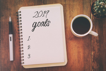 Top view 2019 goals list with notebook, cup of coffee over wooden desk.