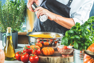 Chef with blender make Pumpkin soup in Kitchen